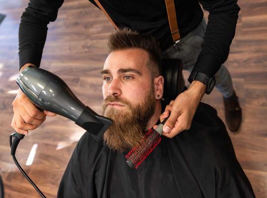 Barbier met mondmasker verzorgt baard van man
